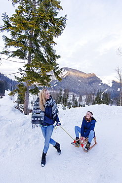 Young woman pulling a sled with woman, Spitzingsee, Upper Bavaria, Germany