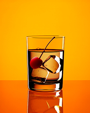 Longdrink with cherry and ice cubes with yellow background, Cocktail, Drink