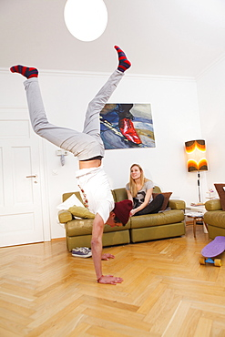 Young man doing a handstand in the lounge