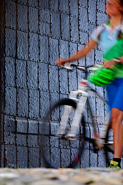 Woman pushing a bicycle, Burghausen, Chiemgau, Bavaria, Germany