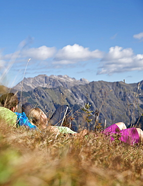 Couple having a break from hiking on a sunny day, Oberstdorf, Bavaria, Germany