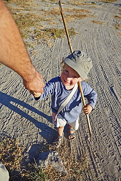 Father and son walking hand in hand, Kubu Island, Makgadikgadi Pans National Park, Botswana