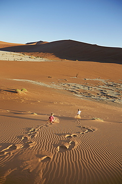 Two boys running down a sand dune, Deadvlei, Sossusvlei, Namib-Naukluft Park, Namibia