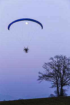 Motor-Paraglider and moon at dusk, Penzberg, Bavaria, Germany