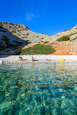 Young women on the beach of a lonely bay on Syphos (Sifnos), Greek Islands, Aegean, Cyclades, Greece