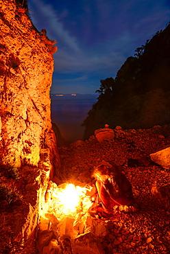 A young woman sitting at the camp fire above the sea near Bacu Mudaloru in the mountainous coast landscape, Golfo di Orosei, Selvaggio Blu, Sardinia, Italy, Europe