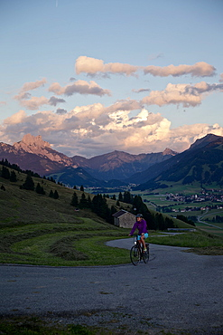 Young woman riding her bike near mountains at sunset, Rote Flueh, Gimpel, Hochwiesler, Tannheimer Tal, Tyrol, Austria