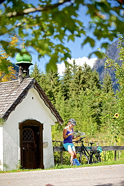 Young female cyclist having a break to read a map / Tannheimer Tal, Tyrol, Austria