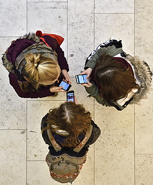 3 Girls chatting with smartphones in a shopping mall, Hamburg, Germany, Europe
