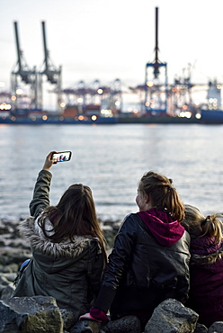 3 girls making selfie pictures at the Elbe River beach, Oevelgoenne, Hamburg, Germany, Europe