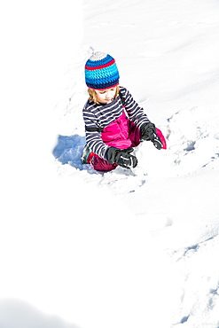 boy building a snowman in winter, Pfronten, Allgaeu, Bavaria, Germany