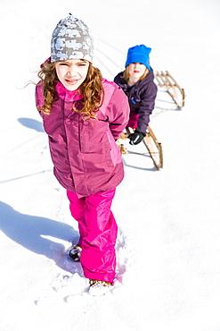 Girl pulling boy on their sleds, Pfronten, Allgaeu, Bavaria, Germany