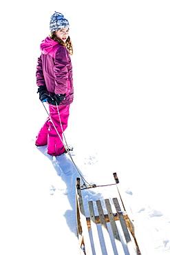 Girl pulling her sledge, Pfronten, Allgaeu, Bavaria, Germany