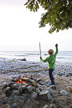 5 years old boy dancing around the campfire, childhood, adventure, outdoor, holiday, Baltic sea, MR, Bornholm, near Gudhjem, Denmark, Europe