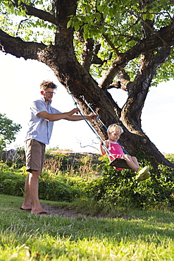 Father pushing young daughter on the swing, Summer, Baltic sea, MR, Bornholm, Svaneke, Denmark, Europe