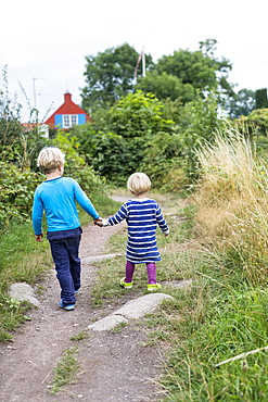 Siblings, children walking hand in hand, hiking trail from Svaneke to Listed, summer, Baltic sea, MR, Bornholm, Svaneke, Denmark, Europe