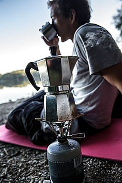 Young man drinking coffee at a lake, Freilassing, Bavaria, Germany