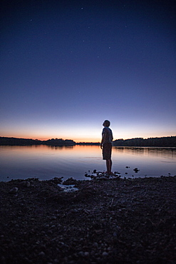 Young man standing at a lake and watching the stars, Freilassing, Bavaria, Germany