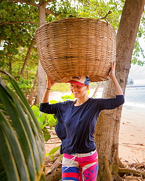 Young woman trying to carry a big basket on her head, Sao Tome, Sao Tome and Principe, Africa