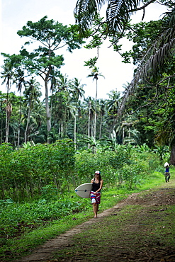 Young female surfer walking on a path through a forest, Sao Tome, Sao Tome and Principe, Africa
