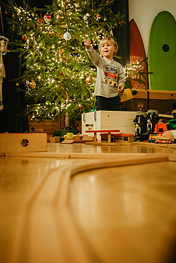 little boy playing with his wooden train in front of the Christmas tree, Christmas, family