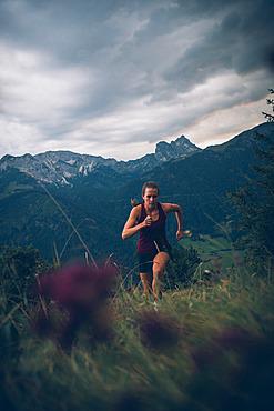Young woman runs in the evening mood at Falkenstein, Allgäu, Bavaria, Germany