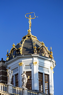 Close-up of building domed turret with gold trim and gold statue on top of dome with blue sky, Brussels, Belgium