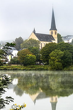 Misty river valley with church in treed area reflecting in the river, Krov, Germany