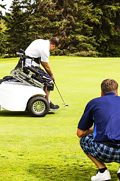 An able bodied golfer teams up with a disabled golfer using a specialized powered golf wheelchair and helps him to line up his putt on a golf green at a golf course, Edmonton, Alberta, Canada