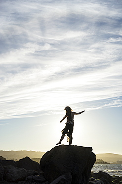 A woman stands balancing on one foot on a rock with a view of the coast at sunset, silhouetted and backlit by the sunlight, San Mateo, California, United States of America