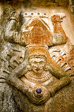 Close-up view of human figure splayed like a toad and holding a purple stone, carved on the side of a Mayan ruin, Tulum, Quintana Roo, Mexico