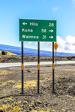 Road sign showing miles to destinations from the Mauna Kea Access Road at its junction with the Daniel K. Inouye Highway (in the picture) also known as the Saddle Road and Hawaii State Route 200 on the Big Island of Hawaii, USA during the summer, Island of Hawaii, Hawaii, United States of America