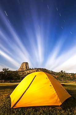 Bright yellow tent and star trails, Devils Tower National Monument, Wyoming, United States of America