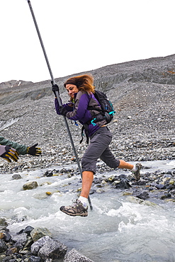 A woman jumps over a swift glacial stream with the aid of a pole near Gulkana Glacier, Alaska, United States of America