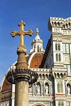 Stone cross with the decorative dome and facade of Florence Cathedral with blue sky, Florence, Tuscany, Italy