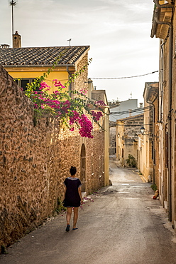Woman walking down a narrow street, Alcudia, Mallorca, Balearic Islands, Spain