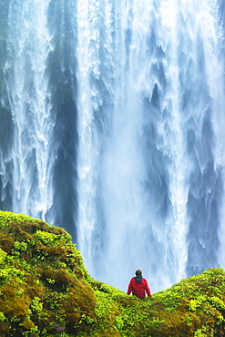 Man sitting on a mossy rock at base of Skogafoss waterfall, Iceland