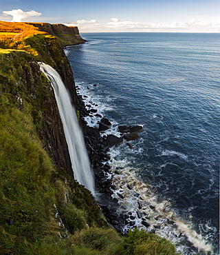 A waterfall flowing over a cliff along the coastline, Isle of Skye, Scotland