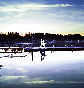 A lifeguard chair on the dock of a tranquil lake at sunrise, Lakeside Bible Camp, Whidbey Island, Washington, United States of America