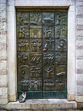 A metal door with pictograms placed in squares over the surface, and a cat sitting on the step, Montenegro