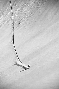 A professional, freeriding snowboarder on a wide open snowy slope making new tracks, British Columbia, Canada