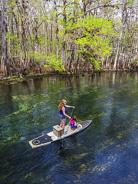 A mother and daughter paddleboard down the stream of freshwater spring, Chiefland, Florida, United States of America