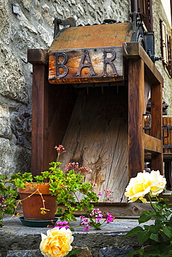 Old wooden bar equipment with flowers in pots, Dolonne, near Courmayeur, Aosta Valley, Italy