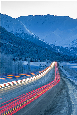 Car lights are blurred down the Seward Highway at dusk in winter, Turnagain Pass, Southcentral Alaska, USA