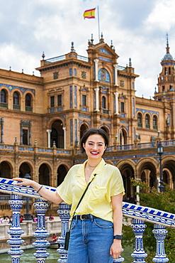 Young female tourist poses at Plaza de Espana, Seville, Andalucia, Spain