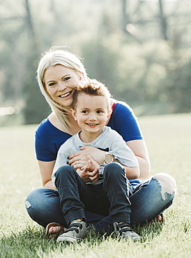 Portrait of mother with young son sitting on the grass in a park, Edmonton, Alberta, Canada