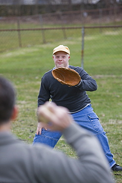 Disabled man playing baseball with his son Disabled man smiling with his son with Down Syndrome