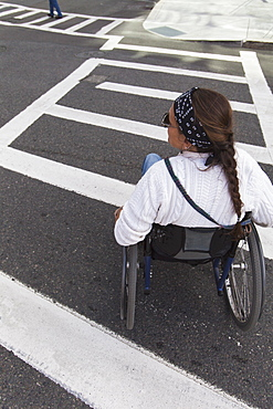 Woman with spinal cord injury in wheelchair crossing street