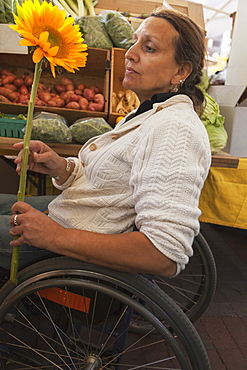 Woman with spinal cord injury sitting in a wheelchair shopping at outdoor market for sun flowers