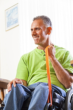 Man with spinal cord injury in a wheelchair using hand and arm strengthening equipment